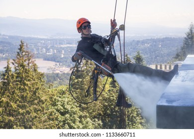 Burnaby Mountain, Vancouver, British Columbia, Canada - July 011, 2018: High rise rope access window cleaner is power washing the building during a hot sunny summer day.