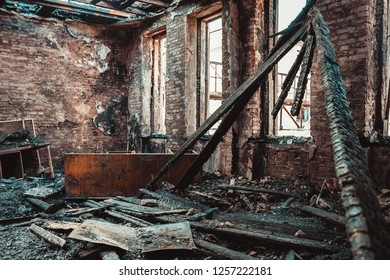 Burned brick house interior with burnt furniture, ruined building room after fire inside, toned