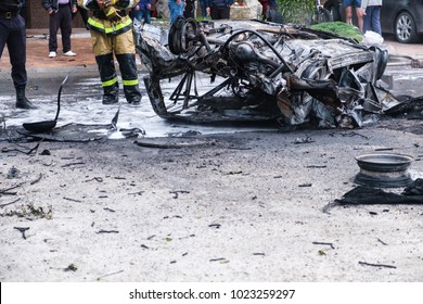 Burned car after an accident on the road. Firefighter standing nearby. Reportage picture of accident