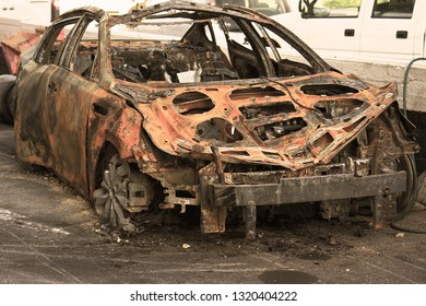 Burned car, burned-out car body. Road wreck accident or arson fire burnt wheel car vehicle junk. Toning.