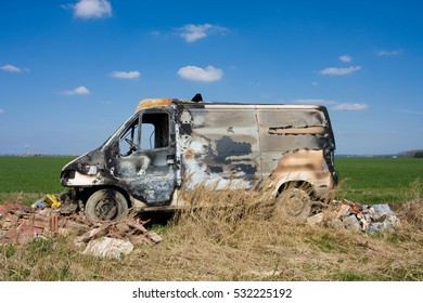 Burned car on the green grass with blue sky on the background