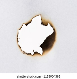 Burned hole on a white paper.