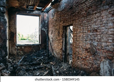 Burned house interior after fire, ruined building room inside, disaster or war aftermath concept.