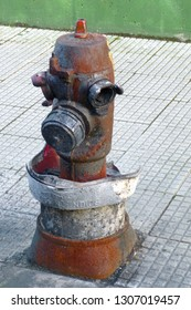 """Burned  hydrant on a sidewalk with rust and melted protective cap with  hydrant written in Spanish (""""boca de incendios"""". Green wall in the background and small squares sidewalk floor tiles."""