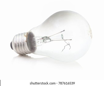 Burned incandescent light bulb with broken wire filament, isolated on the white background with mirror shadow reflection. Non-functional electric light bulb. Burnt lightbulg. Fired-on lamp. Spent lamp