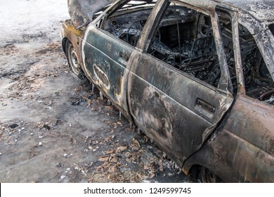 Burned ola car. set fire to cars in parking lot. Deformed fire machine. Consequences of car accident. Damaged by arson. The explosion of gas in the tank machine. Winter and cold.