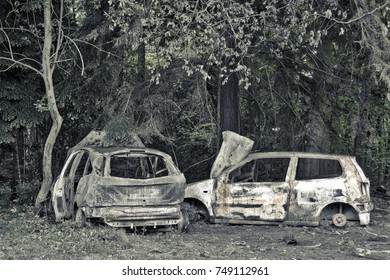 Burned out abandoned crashed derelict cars in car park in the woods