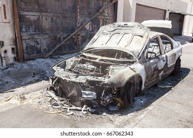 Burned out passenger car after an electrical fire in residental area