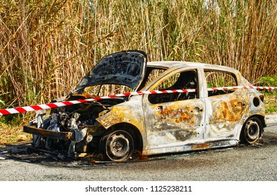 Burned out stolen car abandoned at the side of the road