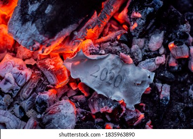 Burned paper with inscription 2020 in the fire. Concept of the end of bad 2020 year and beginning the new better times