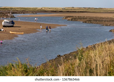 Burnham Overy Staithe, Norfolk/UK - September 2nd 2018: Adults and children enjoying themselves wading in the shallow water of the tidal River Burn estuary at low tide.