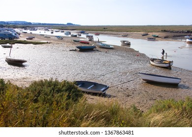 Burnham Overy Staithe, Norfolk/UK - September 2nd 2018: Yachts and boats moored at low tide on the Burn tidal estuary and mother and child paddling.