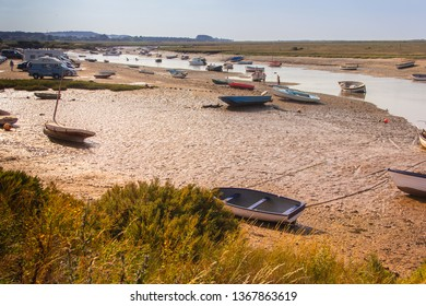 Burnham Overy Staithe, Norfolk/UK - September 2nd 2018: Yachts and boats moored at low tide on the Burn tidal estuary and people paddling and space for text.
