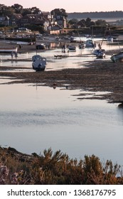 Burnham Overy Staithe, Norfolk/UK - September 2nd 2018: Evening yachts and boats moored at low tide on the Burn tidal estuary with silhouette dogs and people. With text space.