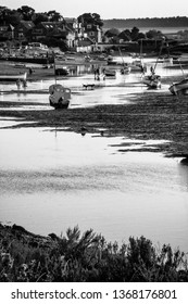 Burnham Overy Staithe, Norfolk/UK - September 2nd 2018: Evening yachts and boats moored at low tide on the Burn tidal estuary with silhouette dogs and people. Black and White. With text space.
