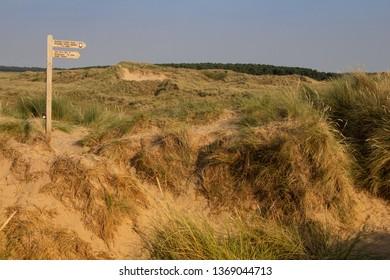 Burnham Overy Staithe, Norfolk/UK - September 2nd 2018: Signpost at Gun Hill with dunes and grass. Horizontal orientation