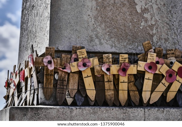 Burnham-on-Crouch, Essex, England - 28 July 2018: WW1 Wooden Memorial Crosses with Faded Paper Poppies on a Cenotaph