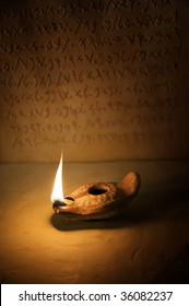 A burning ancient oil lamp with an inscription in the background of the ten commandments written in the Paleo-hebrew script.