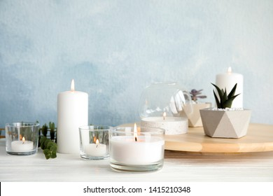 Burning aromatic candle and plants on table. Space for text