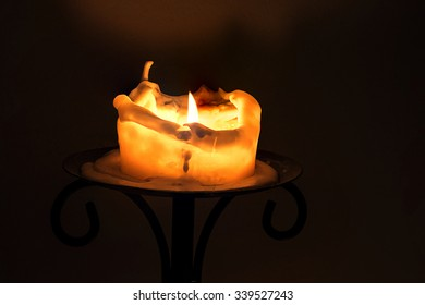 burning big white candle with flame and melting wax on the edge on an iron candlestick against a dark background with copy space