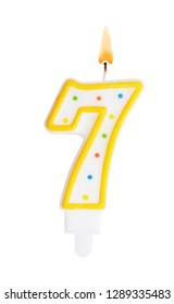 Burning birthday candle isolated on white background, number 7