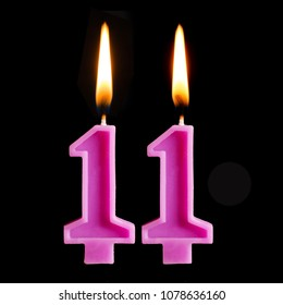 Burning birthday candles in the form of 11 eleven figures for cake isolated on black background.