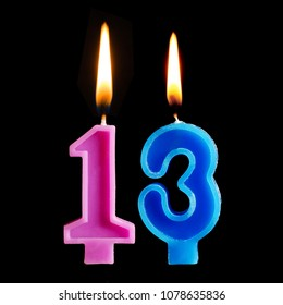Burning birthday candles in the form of 13 thirteen figures for cake isolated on black background.