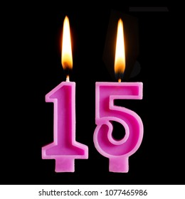 Burning birthday candles in the form of 15 fifteen figures for cake isolated on black background.