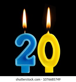 Burning birthday candles in the form of 20 twenty figures for cake isolated on black background. The concept of celebrating a birthday, anniversary, important date, holiday