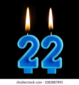 Burning birthday candles in the form of 22 twenty two for cake isolated on black background. The concept of celebrating a birthday, anniversary, important date, holiday