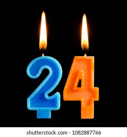 Burning birthday candles in the form of 24 twenty four for cake isolated on black background. The concept of celebrating a birthday, anniversary, important date, holiday