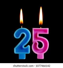 Burning birthday candles in the form of 25 twenty five figures for cake isolated on black background.