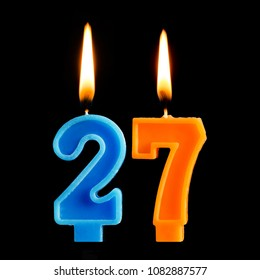 Burning birthday candles in the form of 27 twenty seven for cake isolated on black background. The concept of celebrating a birthday, anniversary, important date, holiday