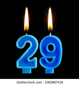 Burning birthday candles in the form of 29 twenty nine for cake isolated on black background. The concept of celebrating a birthday, anniversary, important date, holiday
