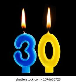 Burning birthday candles in the form of 30 thirty figures for cake isolated on black background. The concept of celebrating a birthday, anniversary, important date, holiday