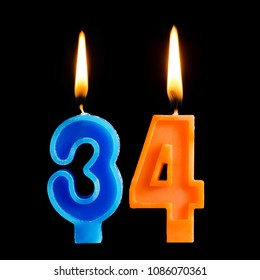 Burning birthday candles in the form of 34 thirty four for cake isolated on black background.