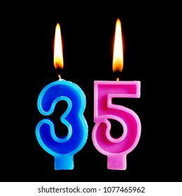 Burning birthday candles in the form of 35 thirty five figures for cake isolated on black background.