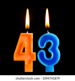 Burning birthday candles in the form of 43 forty three for cake isolated on black background.