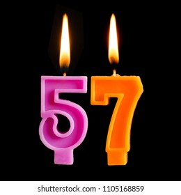 Burning birthday candles in the form of 56 fifty six for cake isolated on black background.