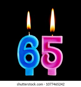 Burning birthday candles in the form of 65 sixty ive figures for cake isolated on black background.