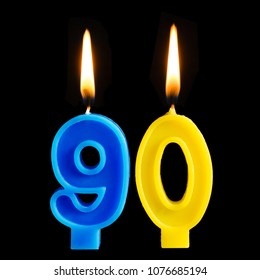 Burning birthday candles in the form of 90 ninety figures for cake isolated on black background. The concept of celebrating a birthday, anniversary, important date, holiday