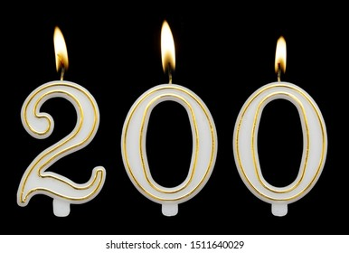 Burning birthday candles isolated on black background, number 200