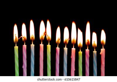 Burning birthday candles on black background