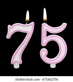 Burning birthday candles on black background, number 75