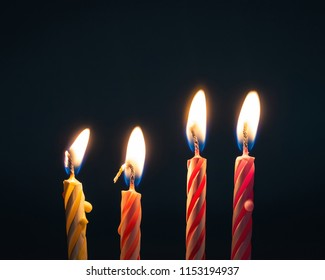 Burning birthday candles on dark background with fire.
