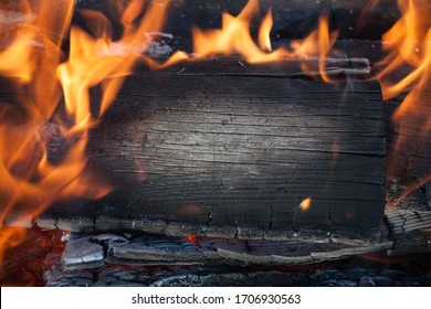 Burning black horizontal board with open red fire flame. Dark grey burned wooden board texture. Burnt wooden Board. Burned scratched hardwood surface. Smoking wood plank background.