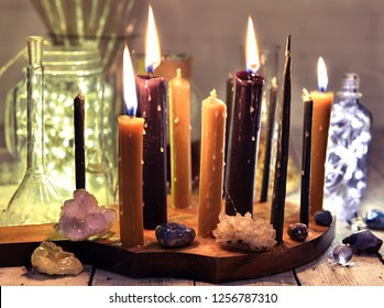 Burning black and vintage candles, crystals and mineral stones with shining bottles on table. Magic ritual. Wicca, esoteric and occult background with vintage witch objects
