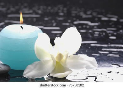 burning blue candles with macro of orchid on wet background