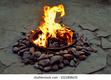 A burning bonfire (flame) surrounded by stones at dusk. Backgrounds and textures.