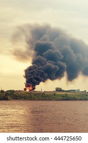 Burning building with flames and black smoke near the water